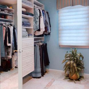 Diseño de armario vestidor unisex, tradicional renovado, grande, con armarios con paneles con relieve, puertas de armario blancas y suelo de travertino