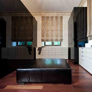 Diseño de armario unisex, contemporáneo, de tamaño medio, con armarios con paneles lisos, puertas de armario negras, suelo de madera oscura y suelo rojo