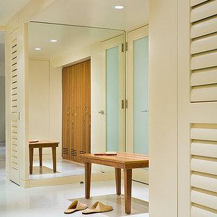 Imagen de vestidor unisex, actual, grande, con armarios con puertas mallorquinas, puertas de armario de madera oscura, suelo de cemento y suelo blanco