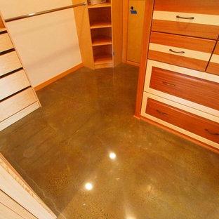Immagine di una cabina armadio unisex classica di medie dimensioni con ante in legno chiaro e pavimento in cemento