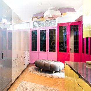 ロサンゼルスの男女兼用コンテンポラリースタイルのおしゃれなフィッティングルーム (フラットパネル扉のキャビネット、黄色いキャビネット、無垢フローリング、茶色い床) の写真
