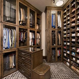 Foto di un grande spazio per vestirsi per uomo chic con ante di vetro, ante in legno bruno e pavimento multicolore