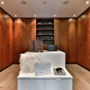 Photo of a contemporary gender-neutral walk-in wardrobe in Toronto with flat-panel cabinets, medium wood cabinets, light hardwood floors and beige floor.