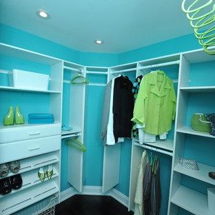 Modelo de armario vestidor unisex, moderno, de tamaño medio, con armarios abiertos, puertas de armario blancas, suelo de madera oscura y suelo marrón