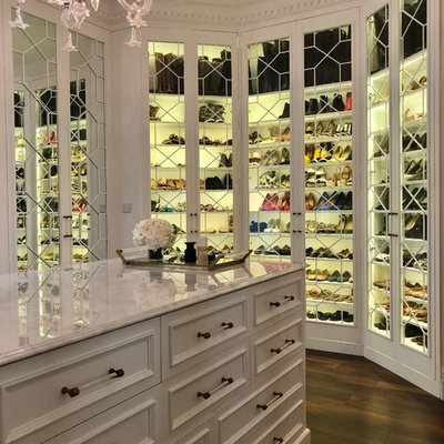 Example of a transitional dark wood floor and brown floor walk-in closet design in Other with glass-front cabinets and white cabinets