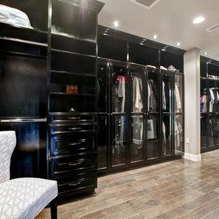 Ejemplo de armario vestidor unisex, actual, extra grande, con armarios tipo vitrina, puertas de armario negras y suelo de madera en tonos medios