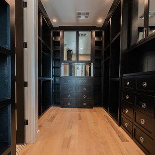 Imagen de armario vestidor unisex, moderno, grande, con puertas de armario negras y suelo de madera clara