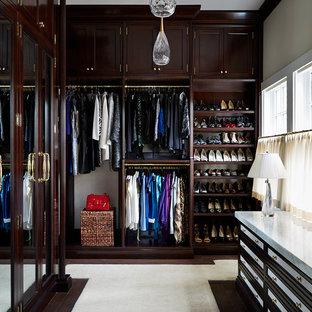 Aménagement d'un très grand dressing classique neutre avec des portes de placard en bois sombre, un sol en bois foncé et un placard avec porte à panneau encastré.