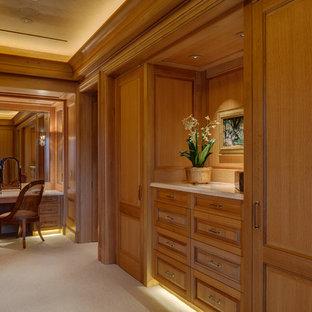 Neutrales Klassisches Ankleidezimmer mit Ankleidebereich, profilierten Schrankfronten, hellbraunen Holzschränken, Teppichboden und beigem Boden in Houston
