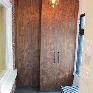 Ejemplo de armario vestidor actual, de tamaño medio, con armarios con paneles lisos, puertas de armario de madera oscura y suelo de pizarra