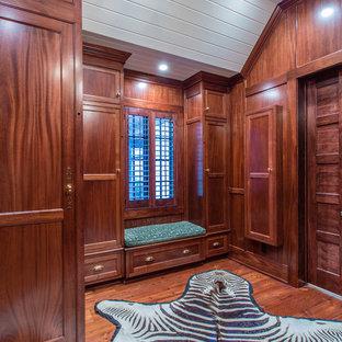 Diseño de vestidor de hombre, ecléctico, grande, con puertas de armario de madera oscura y suelo de madera en tonos medios