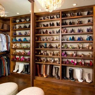 Imagen de armario vestidor de mujer, clásico, grande, con suelo de madera oscura, armarios abiertos y puertas de armario de madera oscura