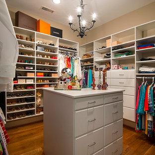 Foto di uno spazio per vestirsi per donna moderno di medie dimensioni con ante bianche, pavimento in legno massello medio, pavimento marrone e ante lisce
