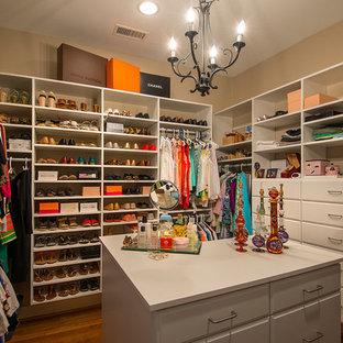 Foto di uno spazio per vestirsi per donna minimalista di medie dimensioni con ante bianche, pavimento in legno massello medio, ante con bugna sagomata e pavimento marrone