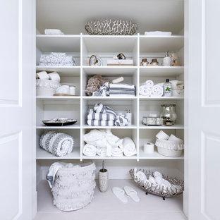 Immagine di un piccolo armadio o armadio a muro unisex con ante bianche, pavimento in gres porcellanato e pavimento bianco