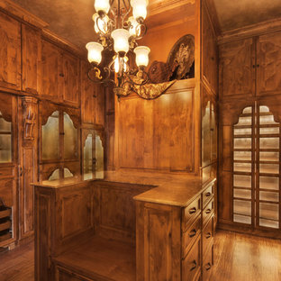 Inspiration for a mid-sized rustic gender-neutral medium tone wood floor walk-in closet remodel in Dallas with raised-panel cabinets and dark wood cabinets