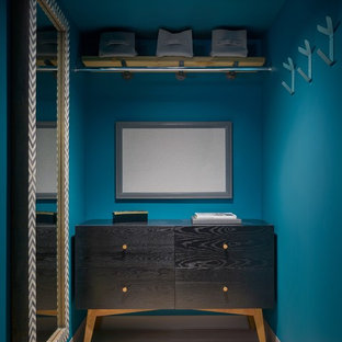 Modelo de vestidor unisex, contemporáneo, de tamaño medio, con armarios con paneles lisos, puertas de armario negras, suelo de baldosas de porcelana y suelo beige