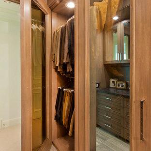 Ejemplo de vestidor de hombre, tradicional, grande, con armarios tipo vitrina, puertas de armario de madera oscura y suelo de piedra caliza