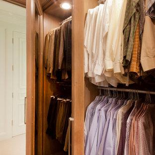 Ispirazione per un grande spazio per vestirsi per uomo classico con ante di vetro, ante in legno scuro e pavimento in pietra calcarea