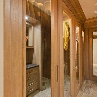 Großes Klassisches Ankleidezimmer mit Schrankfronten mit vertiefter Füllung, hellbraunen Holzschränken und Kalkstein in Omaha