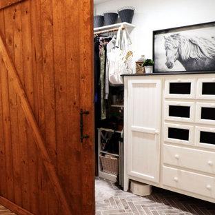 Inredning av ett lantligt mellanstort walk-in-closet för kvinnor, med tegelgolv och flerfärgat golv