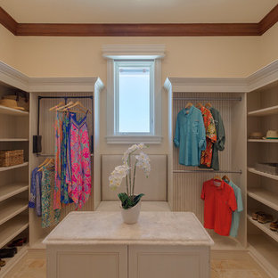 This is an example of a large beach style gender neutral walk-in wardrobe in Miami with beaded cabinets, white cabinets, travertine flooring and beige floors.