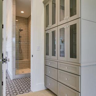Modelo de armario vestidor unisex, de estilo de casa de campo, de tamaño medio, con armarios tipo vitrina, puertas de armario grises y moqueta