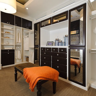 Example of a trendy walk-in closet design in Austin with dark wood cabinets