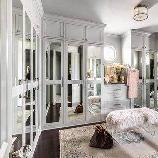Transitional women's walk-in wardrobe in Houston with shaker cabinets, green cabinets, dark hardwood floors and brown floor.