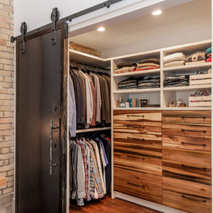 Industrial gender-neutral walk-in wardrobe in Other with flat-panel cabinets, medium wood cabinets, laminate floors and brown floor.