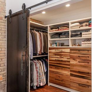 Cette image montre un dressing urbain neutre avec un placard à porte plane, des portes de placard en bois brun, sol en stratifié et un sol marron.