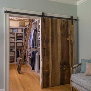 Mid-sized cottage medium tone wood floor walk-in closet photo in Boston with open cabinets and white cabinets