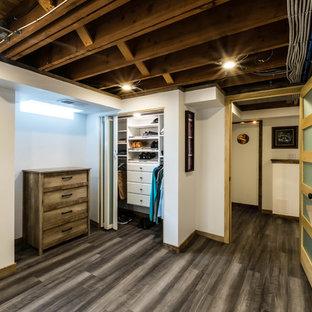 Ejemplo de armario unisex, rural, de tamaño medio, con armarios con paneles lisos, puertas de armario blancas, suelo vinílico y suelo marrón