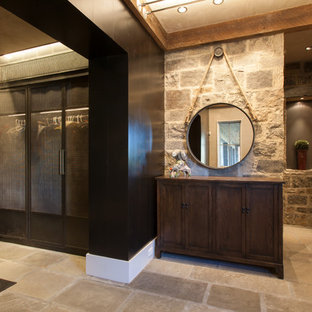 This is an example of a rustic gender neutral wardrobe in Denver with travertine flooring, recessed-panel cabinets and dark wood cabinets.