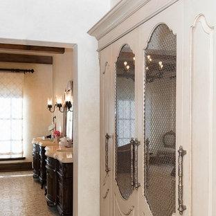 Ejemplo de armario vestidor unisex, mediterráneo, grande, con armarios con paneles empotrados y puertas de armario marrones