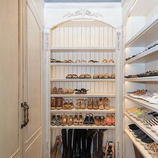 Foto de armario vestidor de mujer, mediterráneo, grande, con armarios con paneles empotrados, puertas de armario beige, suelo de madera oscura y suelo blanco