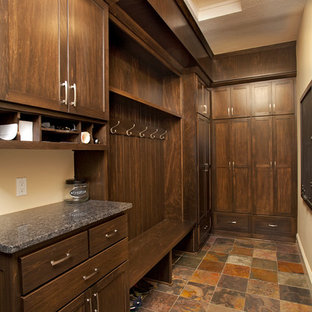 Walk-in closet - mid-sized rustic gender-neutral terra-cotta floor walk-in closet idea in Minneapolis with shaker cabinets and dark wood cabinets