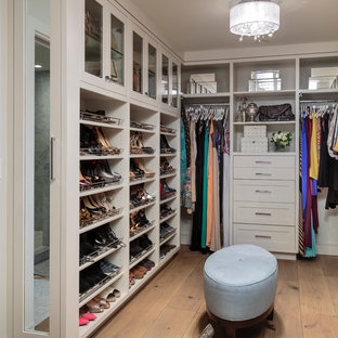 Large transitional women's light wood floor walk-in closet photo in Orange County with open cabinets and white cabinets