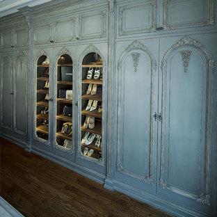 Modelo de armario vestidor de mujer, mediterráneo, grande, con armarios con paneles con relieve, puertas de armario grises, suelo de madera oscura y suelo marrón