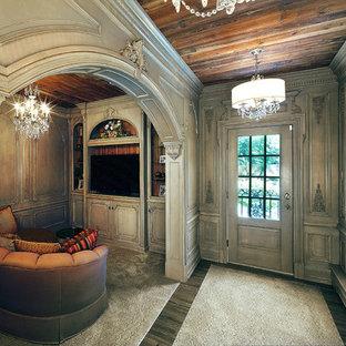 Idee per una grande cabina armadio per donna mediterranea con ante con bugna sagomata, ante grigie, parquet scuro e pavimento marrone