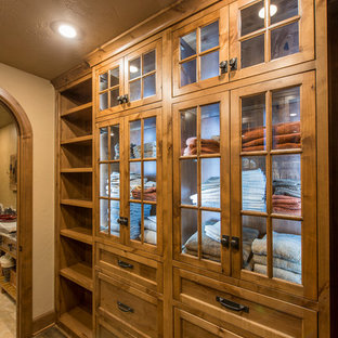 Example of a mid-sized mountain style gender-neutral dark wood floor walk-in closet design in Other with recessed-panel cabinets and medium tone wood cabinets