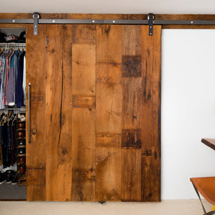 Small country men's built-in wardrobe in New York with flat-panel cabinets, distressed cabinets and carpet.