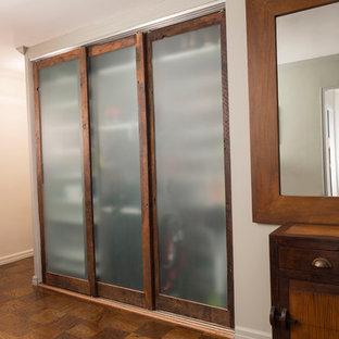 Modelo de armario de hombre, campestre, pequeño, con armarios con paneles lisos, puertas de armario con efecto envejecido y suelo de madera en tonos medios