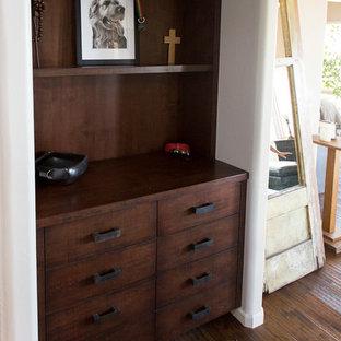 Ejemplo de vestidor de hombre, rústico, grande, con armarios con paneles lisos, puertas de armario con efecto envejecido, suelo de madera oscura y suelo marrón