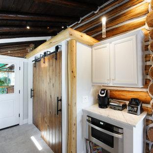 Modelo de armario unisex, clásico, de tamaño medio, con armarios con paneles empotrados, puertas de armario blancas, suelo de cemento y suelo gris