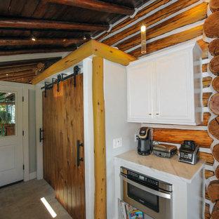 Foto di un armadio o armadio a muro unisex tradizionale di medie dimensioni con ante con riquadro incassato, ante bianche, pavimento in cemento e pavimento grigio