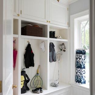 Modelo de armario vestidor unisex, marinero, grande, con armarios con paneles empotrados, puertas de armario blancas, suelo de piedra caliza y suelo gris