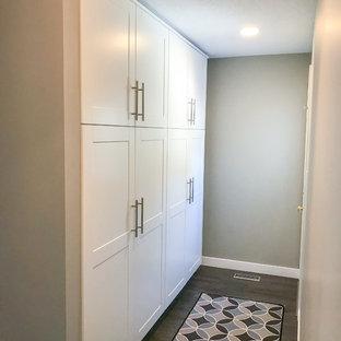 Imagen de armario moderno con armarios estilo shaker, puertas de armario blancas, suelo vinílico y suelo marrón