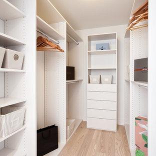 Diseño de armario vestidor minimalista, pequeño, con armarios abiertos, puertas de armario blancas y suelo de madera clara