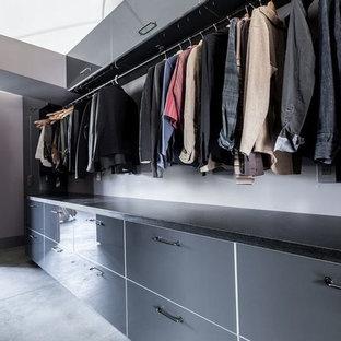 Foto de armario vestidor de hombre, minimalista, grande, con armarios con paneles lisos, puertas de armario grises, suelo de cemento y suelo gris